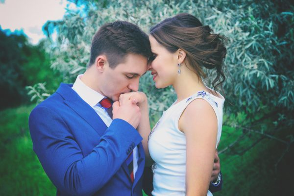 man wearing blue coat kissing her woman's hands with a custom engagement ring