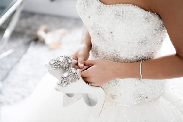 Bride wearing white gown and simple bridal jewellery holding her bridal shoes, at the back of the shoes have gemstones