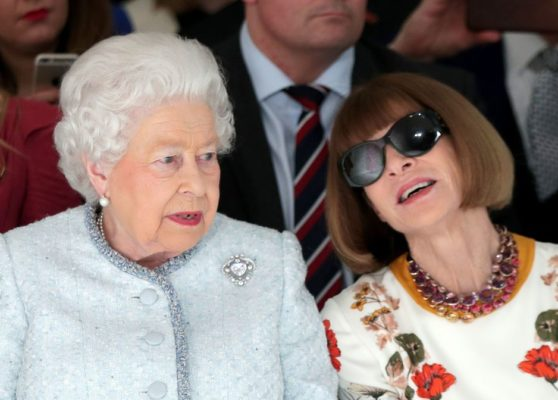 Queen Elizabeth wearing a baby blue coat with cullinan diamond brooch talking to another woman wearing an sunglasses