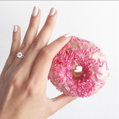 a hand of a woman holding a doughnut with a ring on her ring finger