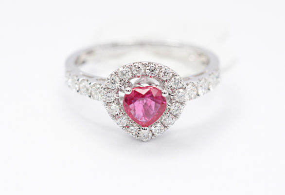 Pink engagement rings design sample of pink ruby held by 3 prongs in white gold metal in a white background