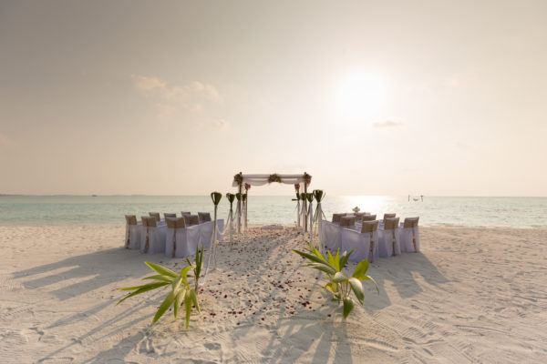 A setup of a beach wedding, alongside the aisle are chairs covered in white cloth perfect wedding destinations