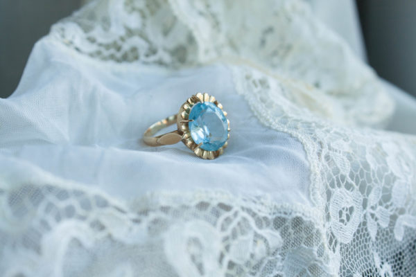 Vintage style engagement rings sample with oval shaped blue sapphire ring placed on white cloth