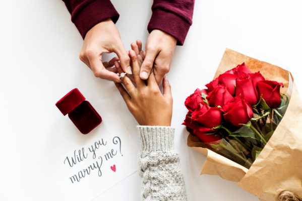 "A hand of a man wears an engagement ring to a woman's ring finger, beside them are a bouquet of red roses and red box and a paper with text ""will you marry me"""