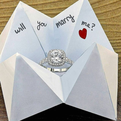 Paper fortune teller with a ring in round cut halo engagement ring setting
