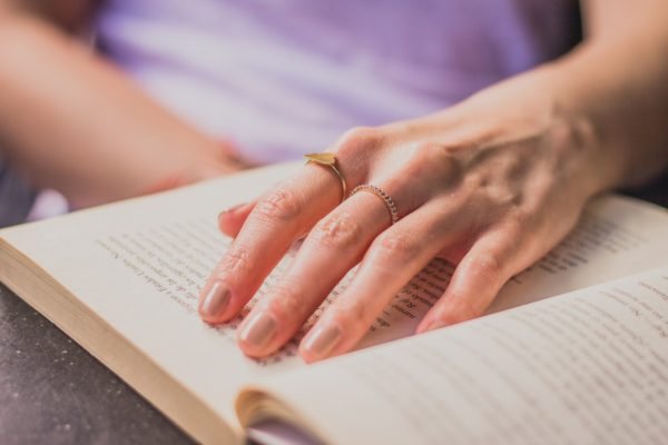 A hand with a simple engagement ring design on the top of a book